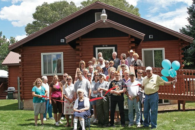 Clients, staff members and organizers of Horizons Specialized Services, members of the Craig Chamber of Commerce staff and ambassadors, and the Moffat County Commission pose Wednesday for a ribbon cutting to commemorate the opening of Horizons' newest group home at 575 Rose Street. Six Horizons clients moved into the home — called the Apple House — on Aug. 2.