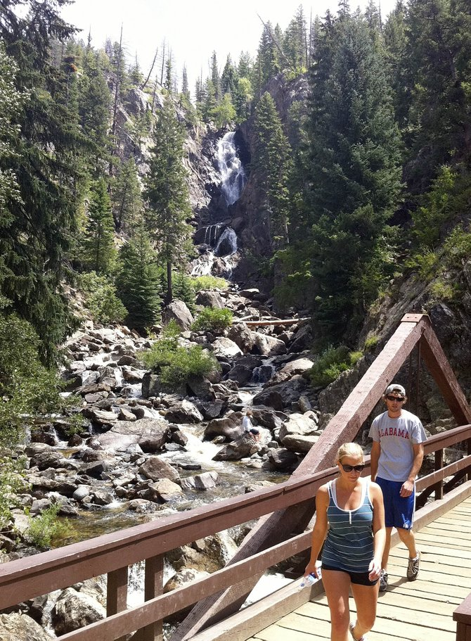 Charlie Deathridge and Danielle Tredway walk along the Fish Creek Falls Trail Thursday afternoon. The parking area is free Saturday and Sunday as part of a back-to-school U.S. Forest Service promotion.