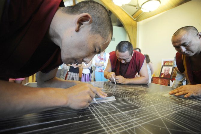 Drepung Loseling monk Sonam Tenzin draws lines that outline the compassion Buddha mandala sand painting they are constructing at Bud Werner Memorial Library. The monks will work for five days on the project, from 10 a.m. to 6 p.m. through Wednesday. Library Hall will be open for visitors to follow the monks' progress as they place grains of colorful sand on the table.