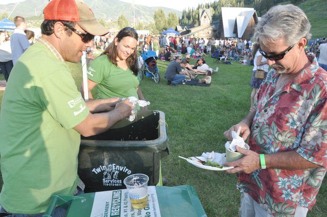 Kenny Reisman, left, helps Mike Smith sort through what trash can be composted Friday at a Free Summer Concert Series event at Howelsen Hill. The Zero Waste Initiative has reduced the amount of trash left behind at the events by composting and recycling as much as 98 percent of the waste.