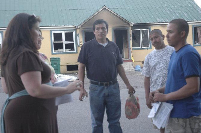 Steamboat resident and American Red Cross volunteer Sarah Cherry, left, talks with Carlos Nataren, right, and Abel Gamarra, center, about clothing and housing options Sunday evening. Nataren and Gamarra are two of 18 people displaced by the Saturday fire at their duplex home at Fourth and Oak streets.