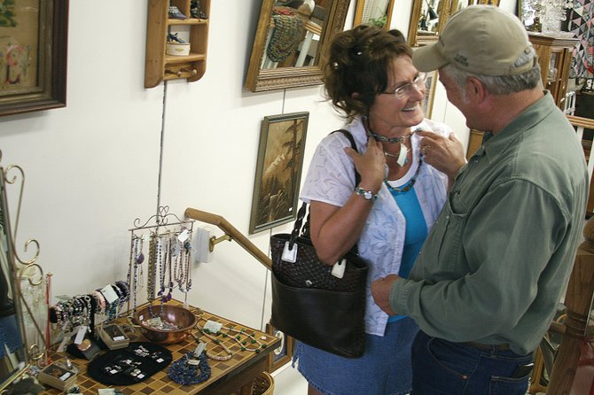 Hayden resident Sally Tyler shows a necklace to her husband, Jim Tyler, on Monday at Favorite Things Antiques & Collectables at 584 Yampa Ave., in downtown Craig. A down economy has created challenges for several downtown businesses that have moved locations or closed operation altogether.