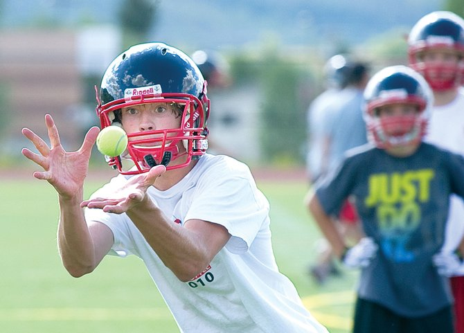 Skyler Kauf runs through a drill using a tennis ball to improve focus during Tuesday's Steamboat Springs High School football practice. This year, the Steamboat Springs Booster Club will support football, as well as 36 other activities and sports.