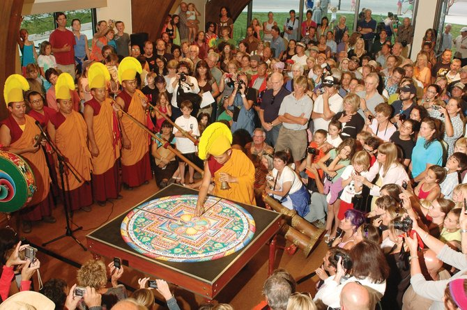 A member of the Drepung Loseling monks begins the transformation of the compassion Buddha mandala before more than 300 intensely curious onlookers in Library Hall at Bud Werner Memorial Library in 2010. The monks will return Tuesday for the first time since then to paint another mandala for the Steamboat community.
