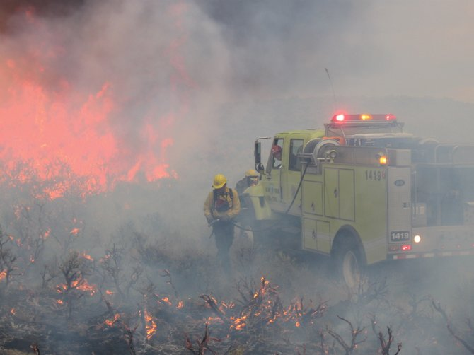 Bureau of Land Management fire crews patrol the boundary of the 7,900-acre Alkali fire north of Maybell in Moffat County on Thursday evening. The fire, burning mostly on private land, is 100 percent contained.