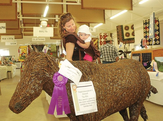Stephanie Martin, of First Impressions of Routt County, and a friend's daughter, Avery Albertini, admire the prize-winning metal sculpture by Troy Allen, of the Elk River Valley, during the Routt County Fair on Friday in Hayden. Allen, a professional welder, created a horse entirely of horseshoe nails. His work earned him the Superintendent's Award given to the most outstanding exhibit in the hall.