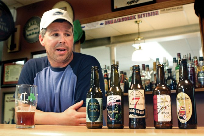 Robert Schenck displays bottles from the five beers he recently brewed Wednesday at his home northwest of Craig. Schenck won grand champion and reserve champion honors with his home-brewed beer at the Moffat County Fair and hopes to start distributing his beers locally in the near future.