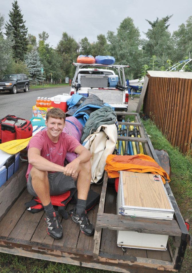 Louis Gutschenritter sits on a trailer full of rafting equipment Thursday that was loaded for a rafting trip to Utah. Gutschenritter will begin to paddle down the Mississippi River on Sept. 3 to raise money for relief efforts in Haiti.