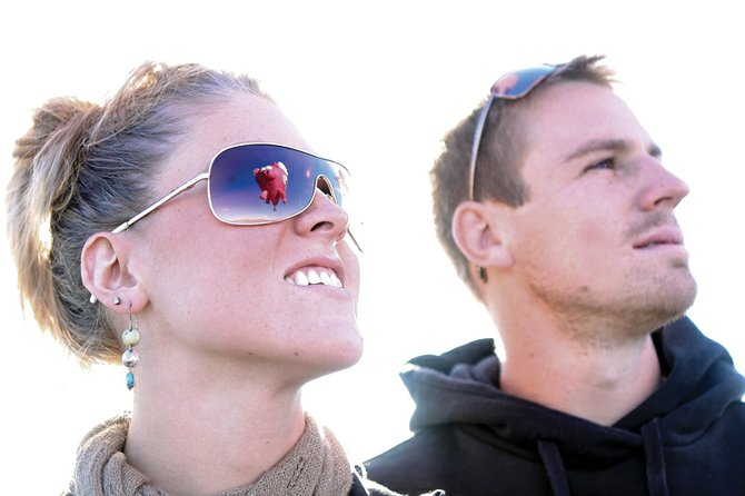 Kelsey Bauman and Mark Niemi watch hot air balloons launch Saturday at the Craig-Moffat County Airport during the Moffat County Hot Air Balloon Festival. About 175 people watched the balloons take to the sky Saturday.