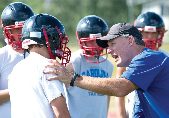 Steamboat Springs High School football line coach Tim Krumrie explains a blocking technique to player Josh Heald during the Sailors practice earlier this week.