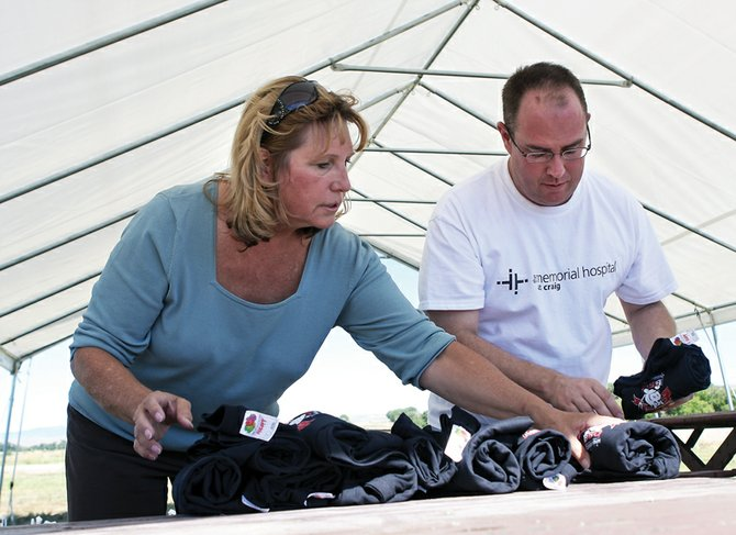 Julie Hanna, left, and Keith Velardo sort T-shirts to give to contestants competing in the upcoming Colorado State BBQ Championship at the Wyman Museum. The event, which will include vendors and entertainment for all ages, is sanctioned by the Kansas City BBQ Society and the Rocky Mountain BBQ Association. 