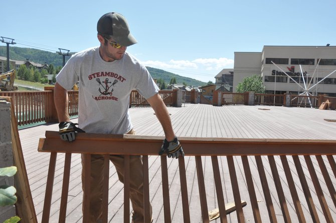 Kurt Bisnette removes a piece of railing  Thursday from the Bear River Bar & Grill deck in Gondola Square. Steamboat Ski and Resort Corp. is replacing the deck with a European-inspired terrace and umbrella bar that will open before the start of the ski season.