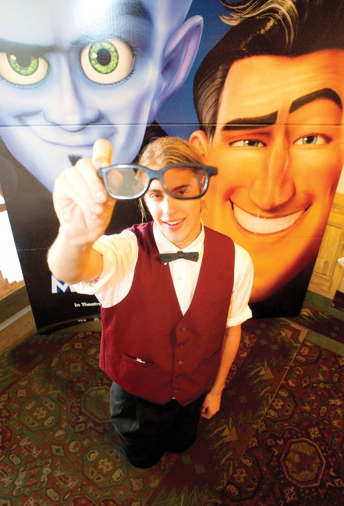 "Chief Plaza Theater employee Westley Thompson holds up a pair of 3-D glasses in front of a billboard for ""Megamind."" The DreamWorks movie is one of several that are expected to be shown in 3-D at the downtown theater."