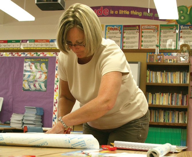 Linda Davis, a fourth-grade teacher at East Elementary School, prepares students' desks Friday in her classroom. Davis, who has taught for 12 years, said she is excited to get to know her students and begin the year. The Moffat County School District resumes classes Monday.