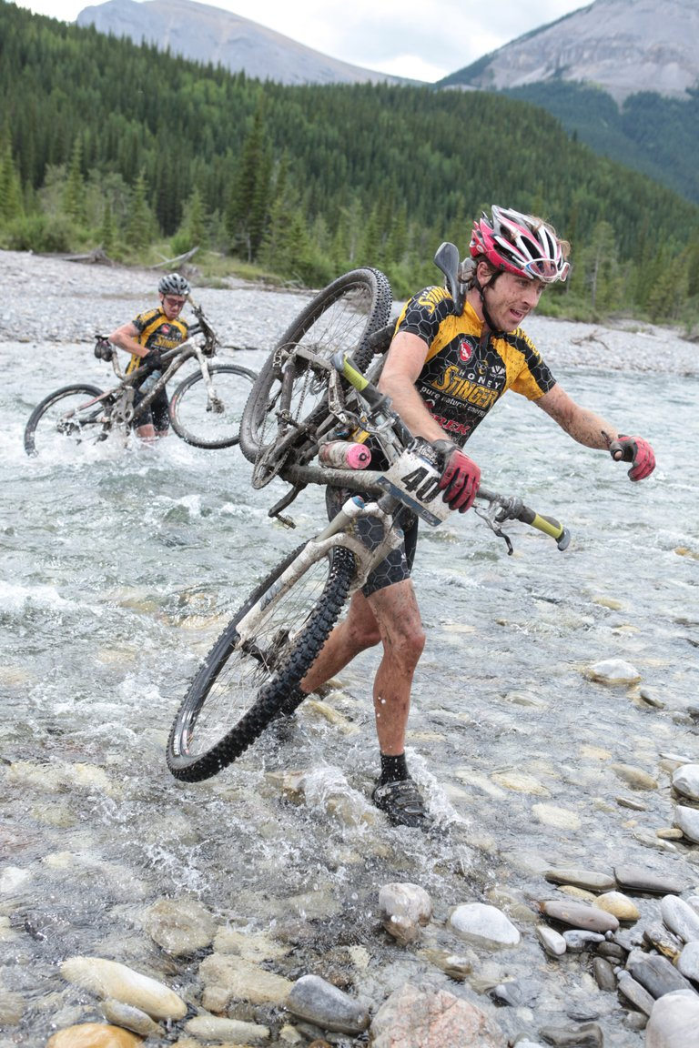 Dax Massey, right, and Nate Bird cross a creek during the TransRockies mountain bike stage race in Canada. Bird has helped put together the Honey Stinger/Trek racing team.