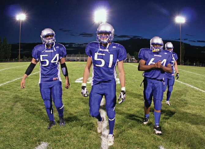 "Moffat County High School football team captains, Angelo ""Hodge"" Raftopoulos, left, C.J. Walt, middle left, Casey Martin, middle right, and Brady Conner, right, walk back to the sideline at halftime of the season opener against Evergreen High School on Friday at the Bulldog Proving Grounds. The Bulldogs fell to the Cougars, 26-22."