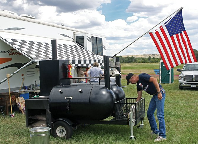 Alan Webber, of Craig, gets his cooker prepared for the first Colorado State BBQ Championship in Craig Friday at the Wyman Museum. This is Webber's seventh competition. He has cooked competitively for four years.