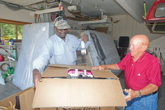 Mamadou Niass, left, gets a helping hand from friend Luther Berntson while packing items to send back to Mauritania in West Africa. Niass sought political asylum in the United States eight years ago and has been collecting items and money to send to his home.