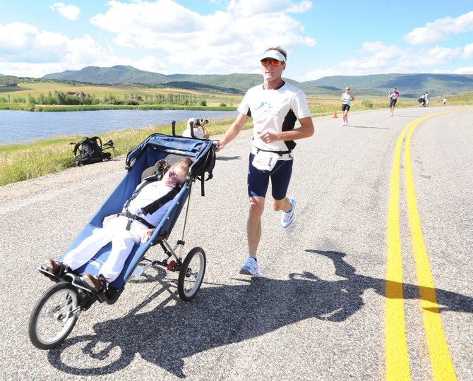 Dennis Vanderheiden runs with Jennifer Roemmich during Sunday's Steamboat Triathlon. Vanderheiden started the Athletes in Tandem organization in 2008, and he competes in triathlons with those who aren't able to compete by themselves. Roemmich, whose parents have lived in Steamboat Springs for 11 years, suffers from cerebral palsy.