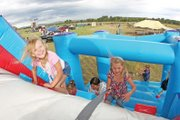 Madison Laman, left, 6, and her sister, Kassadi, 7, climb up the bouncy wall during the Colorado BBQ Championship on Saturday at Wyman Museum. There was also a hay-maze, face-painting, camel rides, fishing pool and a create-your-own-BBQ-sauce station to entertain the children.