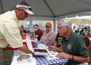 Matt Provost, left, shows a plate of brisket to judge Terry Conci during the Colorado BBQ Championship on Saturday at Wyman Museum. Food was judged based on appearance, tenderness and taste.