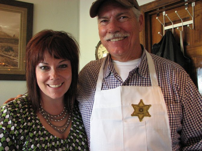 "Ken Battson and his daughter, Linda Battson, pose for a photo at the Fireside Family Restaurant in Baggs, Wyo. Ken, who owns the restaurant, hosted a fundraiser Saturday for Kyle Rosentreter, an injured deputy from the Carbon County Sheriff's Office. The sticker on Ken's apron reads: ""Junior Deputy Sheriff Carbon County."""