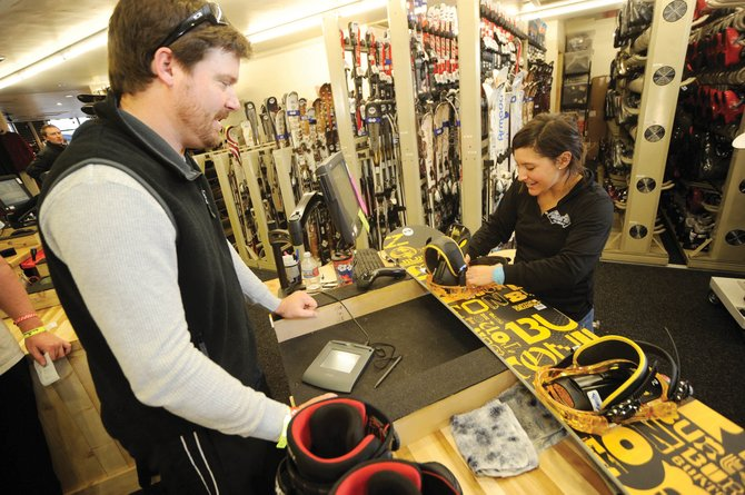 Black Tie Ski Rentals employee Alexa Webster sets up a board for customer David Granstaff last season. The company plans to open a service center in One Steamboat Place.