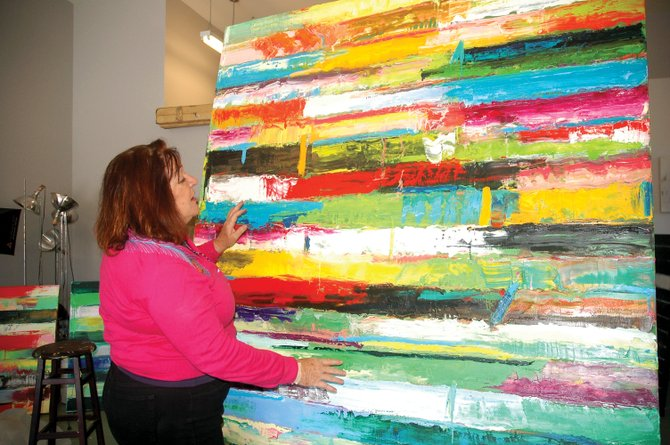 Monroe Hodder explains the emotions behind one of her pieces of abstract art Wednesday in her studio. The local artist's work will be on display at K. Saari Gallery starting tonight at First Friday Artwalk.