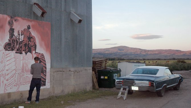 Justin Hayes works on his mural Wednesday night on the wall of a granary warehouse at Yampa Valley Feeds. Because Hayes works as a carpenter during the day, he can only paint in the evenings and on weekends.