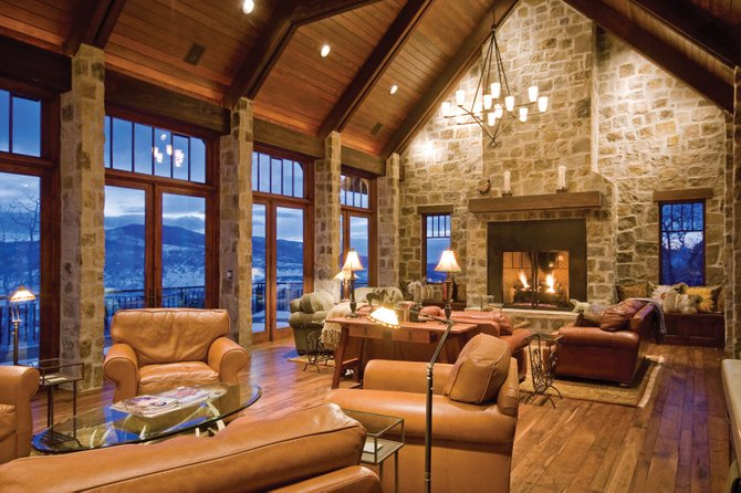 The great room of the home on Deer Clover Lane is dominated by a rustic stone fireplace wall.