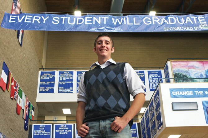 Slade Gurr, a Moffat County High School senior and the student council president, stands in the school's commons area Thursday. The banner above him, which was sponsored by the Colorado Student Center in Craig, is part of a student council initiative to raise MCHS graduation rates.