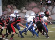 Mason Updike, center, runs through a wall of Aspen defenders Friday. MCHS would be unable to catch the high-flying Skiers, and fell, 46-13.