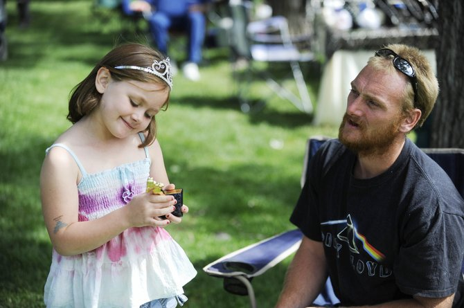 Destiny Hunter, 6, stands next to her father, Ryan Hunter, and admires her Oak Creek Coal Princess trophy after it was awarded to her during Oak Creek Labor Day festivities at Decker Park.
