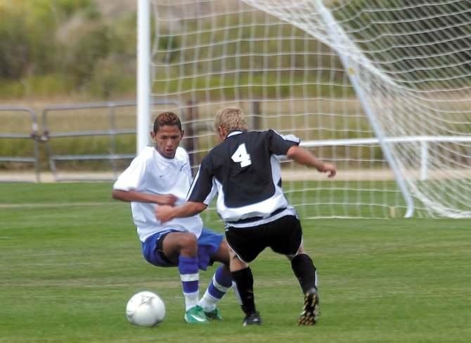Moffat County's Alex Perez, left, battles Saturday with a Montezuma-Cortez High School defender. Perez scored a goal, as the MCHS boys varsity soccer team won, 6-1.