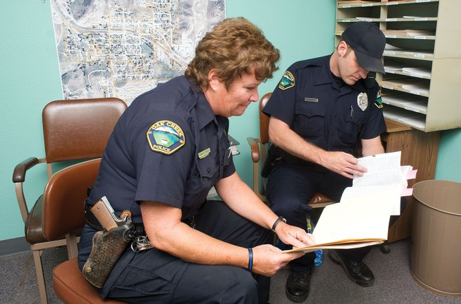Chief Administrative Officer Lance Dunaway, left, and Senior Officer Eileen Rossi go over some paper work inside Rossi's office at the Oak Creek Police Department. Rossi will head to Arizona for the winter after her contract with the town expires Wednesday.