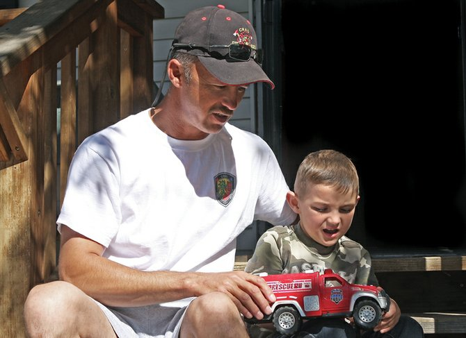 Craig Fire/Rescue lieutenant Troy Hampton, left, sits with his nephew, Jeremiah Price, 5, while the boy plays with a toy fire truck Friday in front of the Price home on Legion Street. Jeremiah was diagnosed with Duchenne muscular dystrophy in April 2009. Hampton, along with other members of the Craig Fire/Rescue team, raised more than $5,000 locally to benefit the Muscular Dystrophy Association.