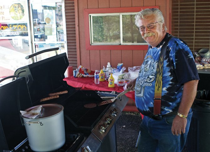 Kirk Libbee cooks free hotdogs and hamburgers for Saturday's customer appreciation day at Quality Plus One Hour Photo in Craig. Kirk, who sold the store to his son Robert Libbee in 2007, said the business has kept up with the changing times.