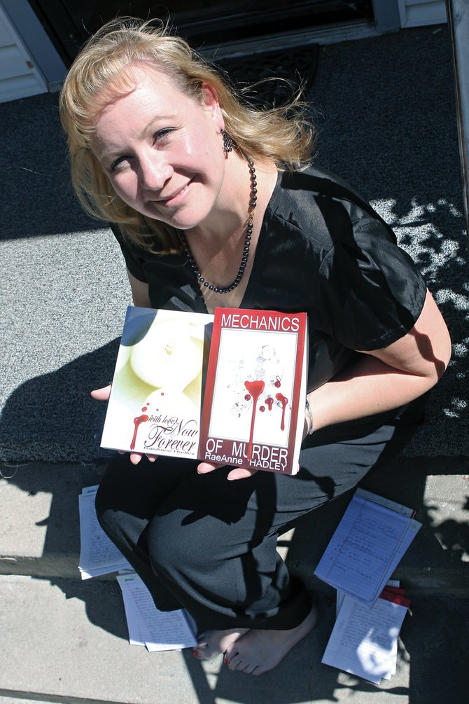 "RaeAnne Hadley shows off two books she has had published, ""With Love; Now and Forever,"" on the left, published in May 2010, and ""Mechanics of Murder,"" published in 2008, Tuesday on her front porch. Hadley does most of her writing on either her front or back porch in long hand before transcribing the final piece into digital format."
