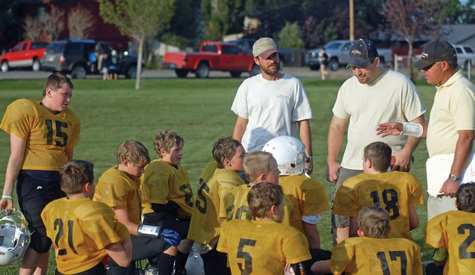 Coach Steve Hafey, far right, talks to his team, the Steelers, about the importance of improving their offensive output following their 7-0 victory Tuesday night against the Jets in fifth- and sixth-grade Doak Walker football action.