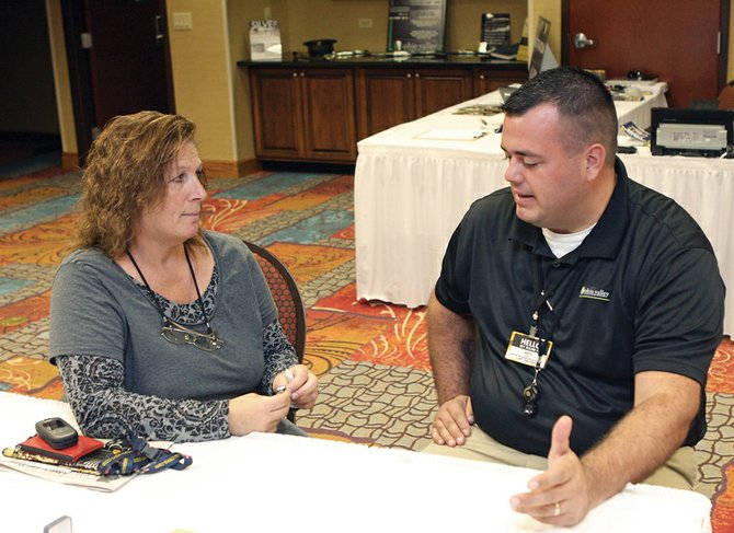 Craig resident Becky Plummer, left, speaks with Jaryd Gerhart, a manager with Ohio Valley Gold & Silver Refinery, over the value of a family heirloom Tuesday at the Hampton Inn & Suites meeting room.