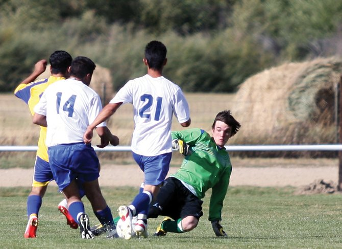 Senior goalkeeper Dustin Carlson, right, slides to make a stop during a game against Roaring Fork High School on Sept. 9 at Loudy-Simpson Park. The 4-0 Bulldogs will open league play at 6 p.m. today against the 3-0-1 Sailors in Steamboat Springs.