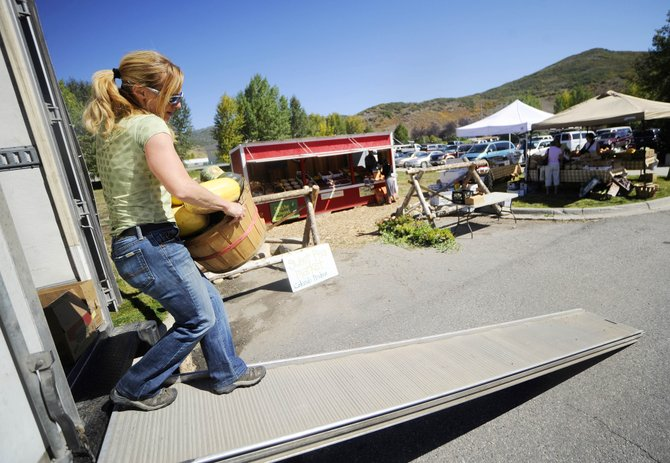 Sweet Pea Market and Cafe employee Romy Klinger unloads produce Wednesday at the Sweet Pea stand near Ace at the Curve.  The Routt County Board of Health revoked Sweet Peas retail food establishment license Tuesday, closing its downtown location until at least Nov. 15 because of health code violations.