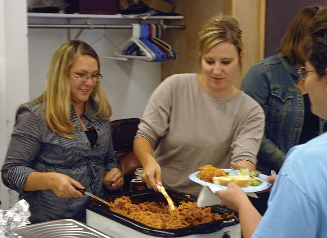 Sandrock Elementary School staff members Andrea Medina, left, and Megan Charchalis serve a plate of spaghetti during a fundraiser Thursday night for Craig resident Gary Thompson at the Veterans of Foreign Wars Post 4265. Thompson was diagnosed with multiple myeloma in August, and employees of the elementary school, where Thompson's wife Anna works as an aide, joined to raise money for his medical expenses.
