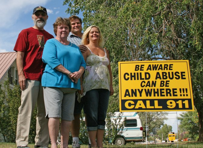 "Lily Madrene Hill, front left, of Wichita, Kan., stands near a child abuse awareness sign that is an integral piece of ""The Grandmother Project,"" a program she spearheaded with another Kansas woman. Hill is pictured with her husband, Jerry, left, and Craig residents Van Austin and Sandy Crain at Austin's home at 760 Yampa Ave."