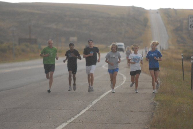 Todd Trapp, far left, head coach of the Moffat County High School cross country team, leads his runners down U.S. Highway 40 in preparation for the team's fall invitational Saturday. The team performed well at last weekend's Liberty Bell Invitational, with senior Chris Zirkle placing first and junior Alfredo Lebron placing second in the boys Division 3 rankings. The boys and girls teams both placed fourth overall.