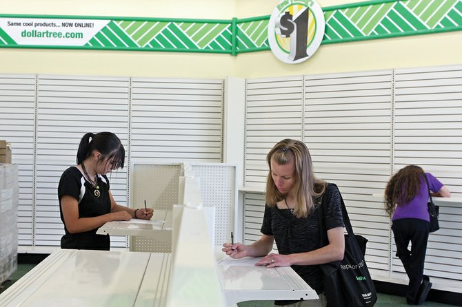 Shene Chamberlain, left, and Rochelle Ellifritz, middle, fill out applications Wednesday at the Dollar Tree in the Centennial Mall. The store had a hiring event to fill positions in preparation for its Oct. 12 opening.