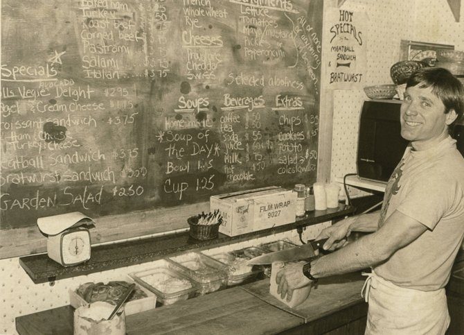 Larry Caveny, co-owner of Rolls Choyce, slices a brick of cheese as he begins making one of the shop's various sandwiches in this April 1985 photo. Rolls Choyce was located in Ski Time Square.
