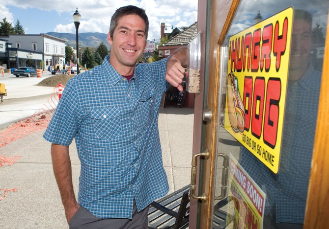 Brad Somers stands near the kiosk in Old Town Square where he will open The Hungry Dog stand. The business will offer downtown visitors a variety of hot dogs as well as nachos, chili and other foods. 