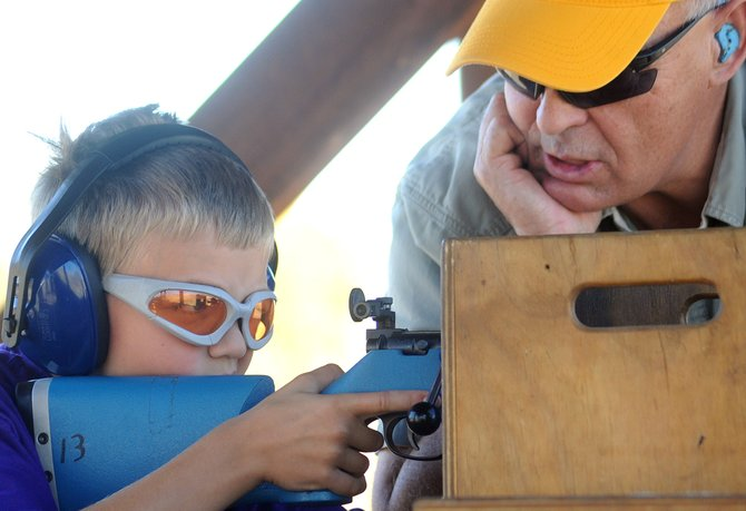 Max Pinto, 9, takes aim with a rifle as Mike Curzon offers advice Sunday during the second annual Lorna Farrow Memorial Fun Shoot.