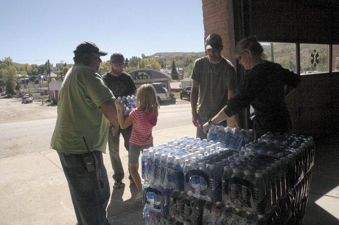 Theresa Kelliher, of the Oak Creek Fire Protection District, right, talks with Oak Creek resident J.D. Fuchs about the town's Saturday night water leak. Free water was distributed to residents Sunday at the Main Street fire station. At left, Dusty Schrader, of the fire district, looks on as Theresa's daughter, Megan, hands water to James Singleton.